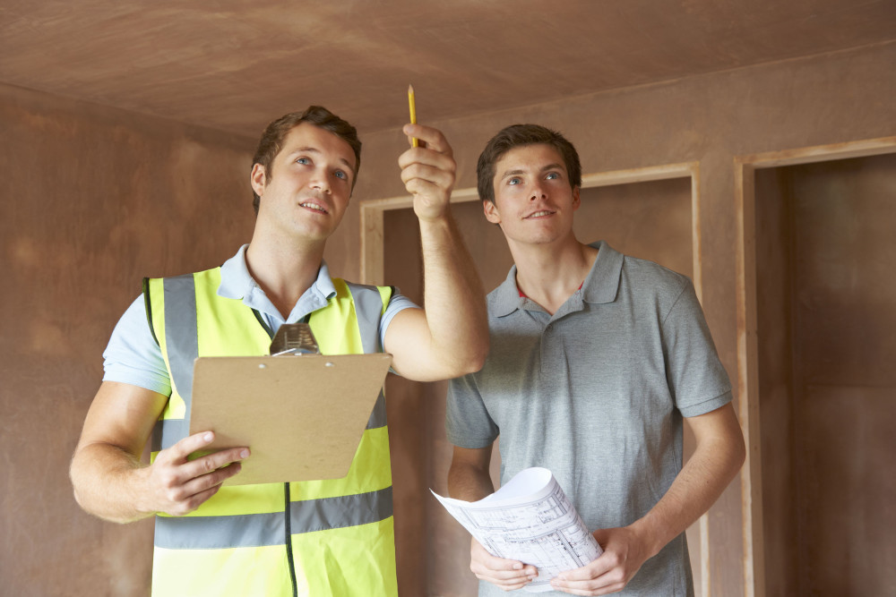 48849294 - Builder And Inspector Looking At New Property