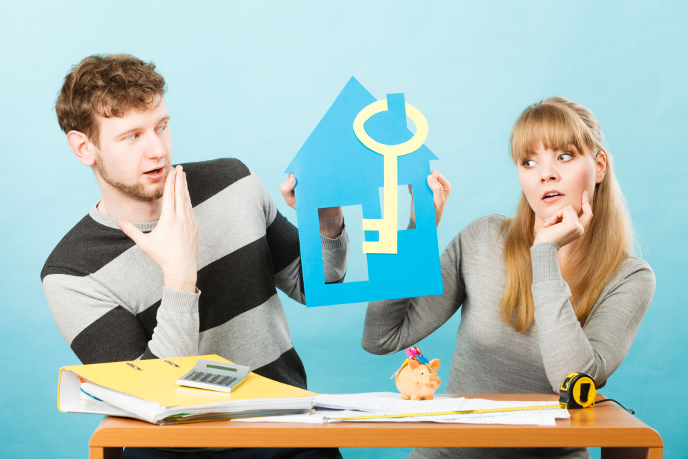 63535189 - Money And Real Estate Problems. Young Worried Couple With Paper Model Of House And Key. Young Marriage Calculate Expenses.