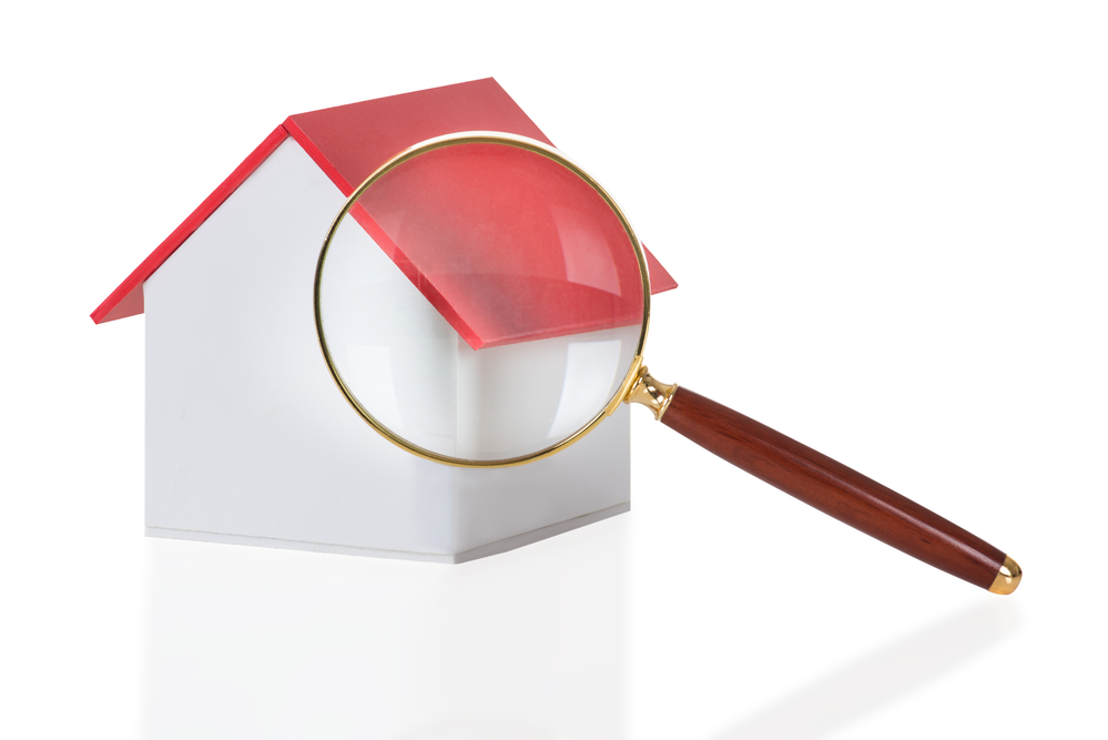 Closeup Of Magnifying Glass And House Model Isolated Over White Background